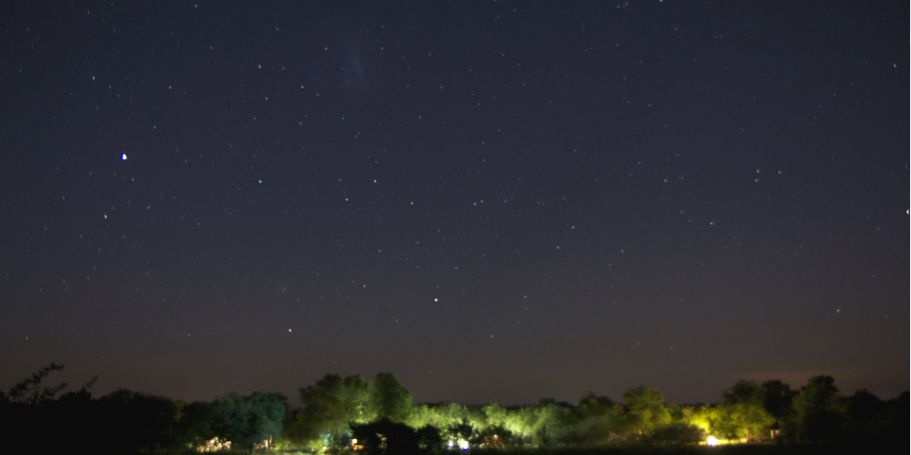 A lit up camp site in the bush, under a starry sky.