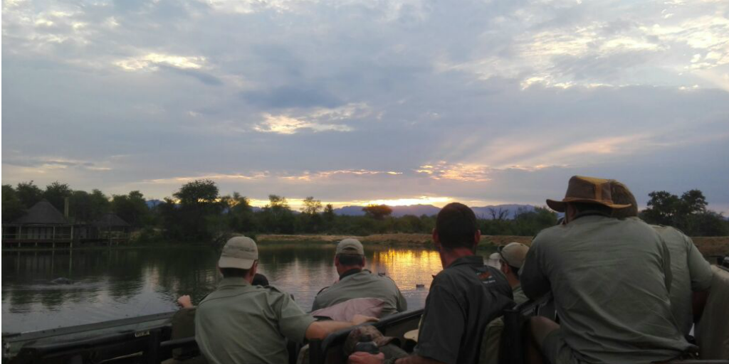 Field guide trainees watching the sunset from a safari vehicle.