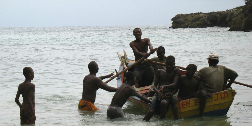 Haitian men boarding a rowing boat in the ocean.