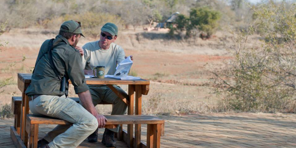 Two Bushwise staff members sitting at a picnic table outside.