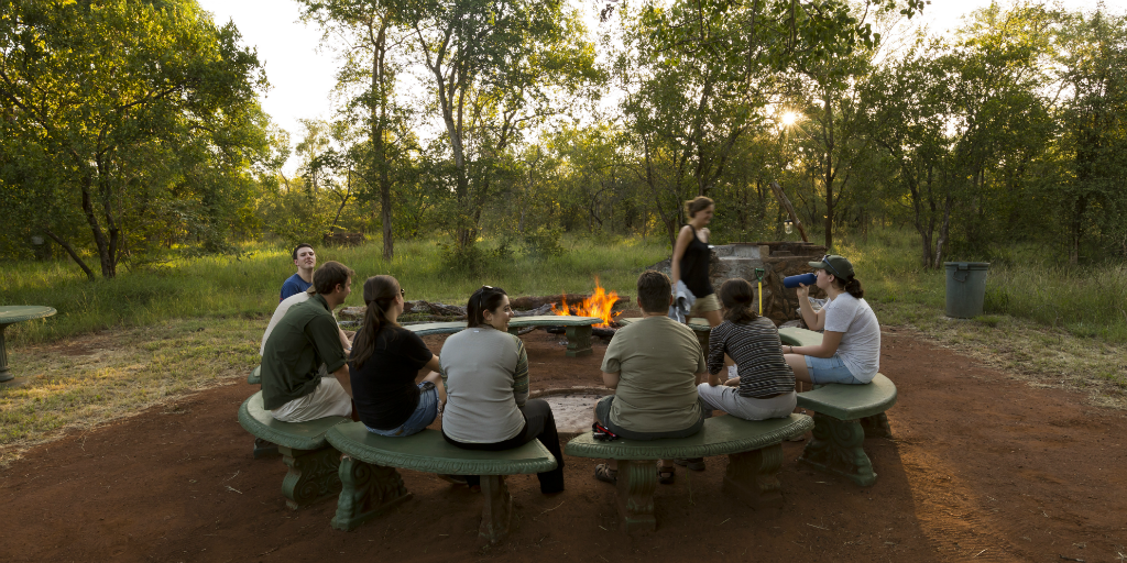 Volunteers share stories around a camp fire