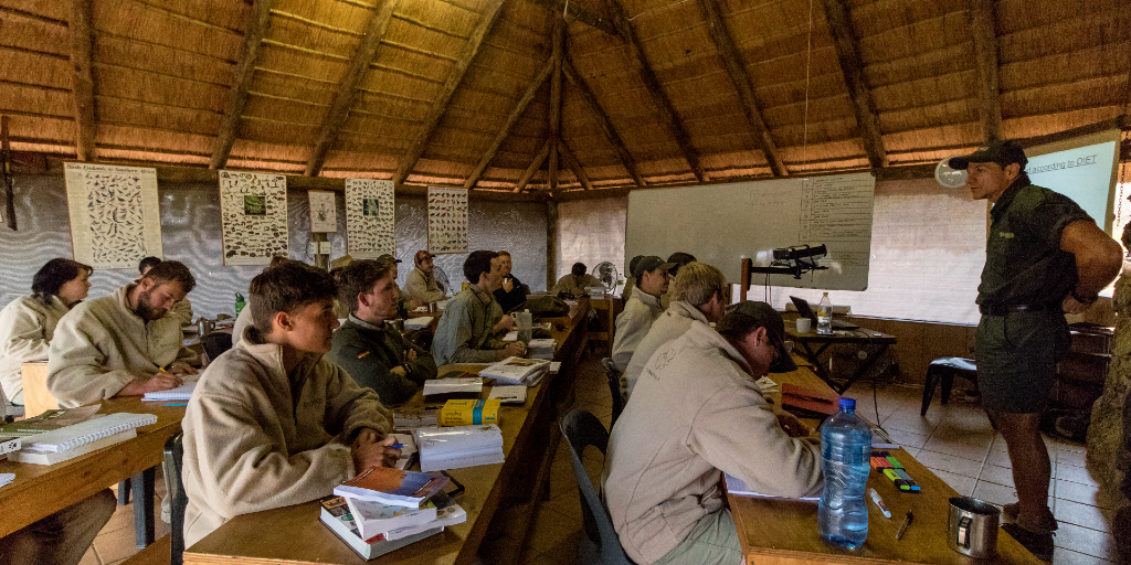 A man presents a class to future wildlife rangers.